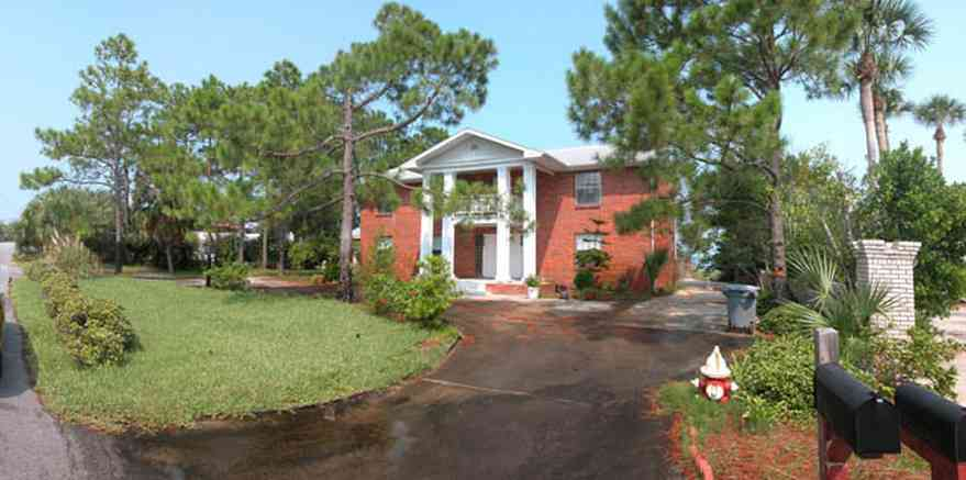 Pensacola-Beach:-235-Sabine-Drive_01.jpg:  colonial architecture, columns, red brick house, pine trees, long-leaf pines, circular driveway