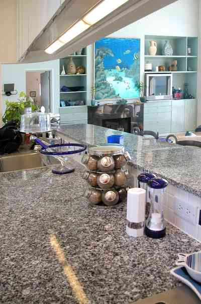 Pensacola-Beach:-Ariola-Drive-Art-Deco-House_27.jpg:  granite countertop, salt and pepper shaker, spice rack, kitchen sink, open floor plan, cake plate, fireplace, marble, wooden floor