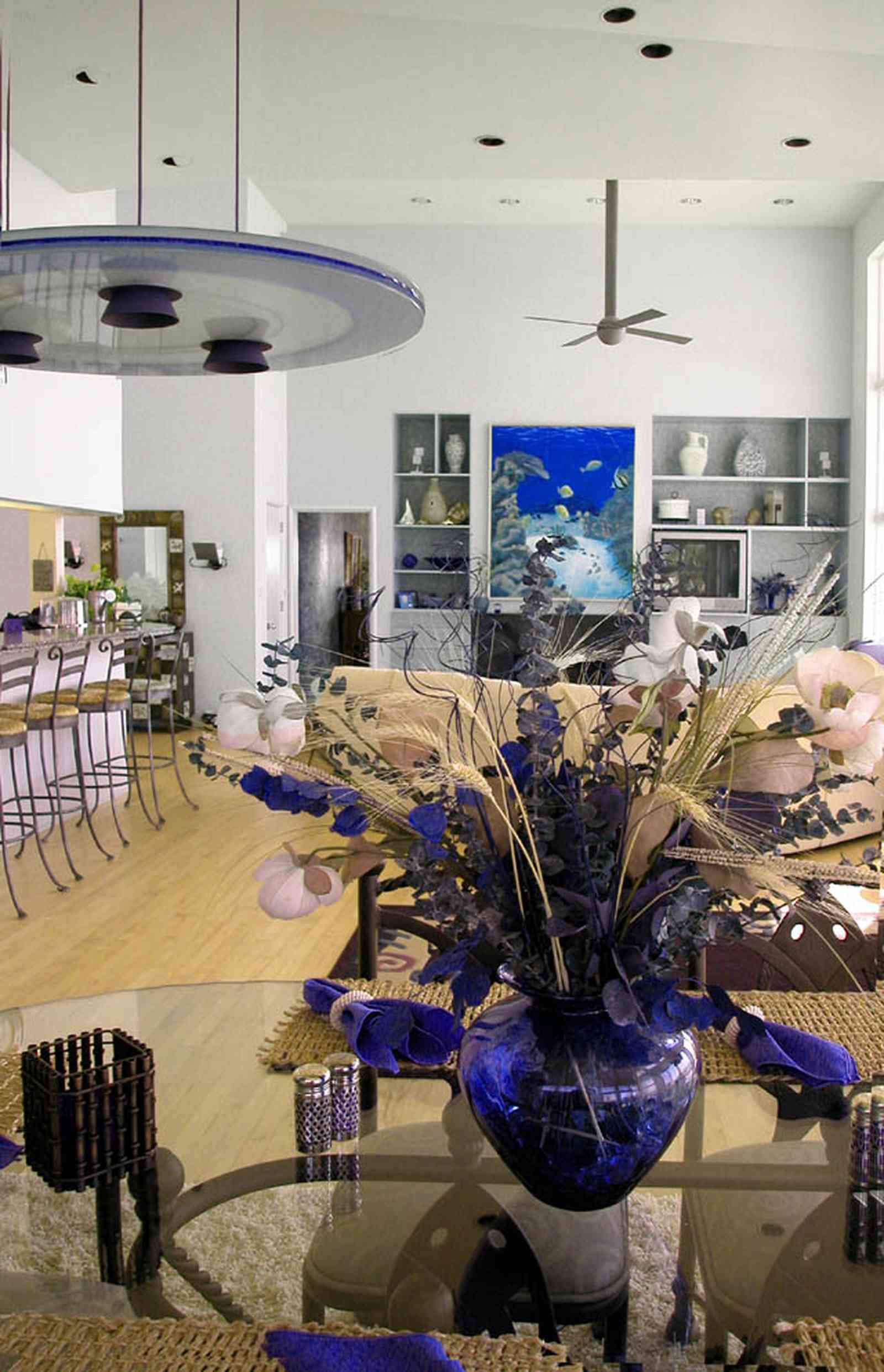 Pensacola-Beach:-Ariola-Drive-Art-Deco-House_29.jpg:  flower arrangement, glass table, open floor arrangement, bar stools, kitchen counter, wooden floors, beach front home
