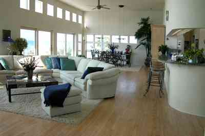 Pensacola-Beach:-Ariola-Drive-Art-Deco-House_31.jpg:  sectional sofa, leather sofa, hassock, beachfront home, coffee table, bar stools, grantite countertop, ceiling fan, patio doors, dining room table, beach