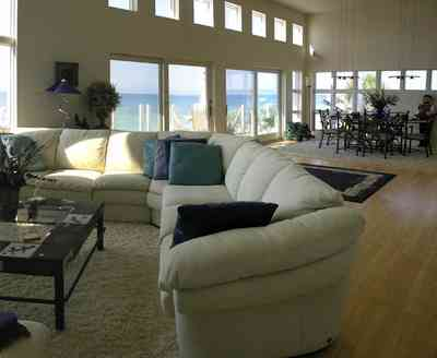 Pensacola-Beach:-Ariola-Drive-Art-Deco-House_32.jpg:  sectional sofa, leather sofa, hassock, beachfront home, coffee table, bar stools, grantite countertop, ceiling fan, patio doors, dining room table, beach