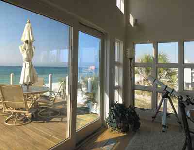 Pensacola-Beach:-Ariola-Drive-Art-Deco-House_33.jpg:  umbrella table, deck, telescope, wood floors, gulf of mexico, windows, palm tree, beachfront view