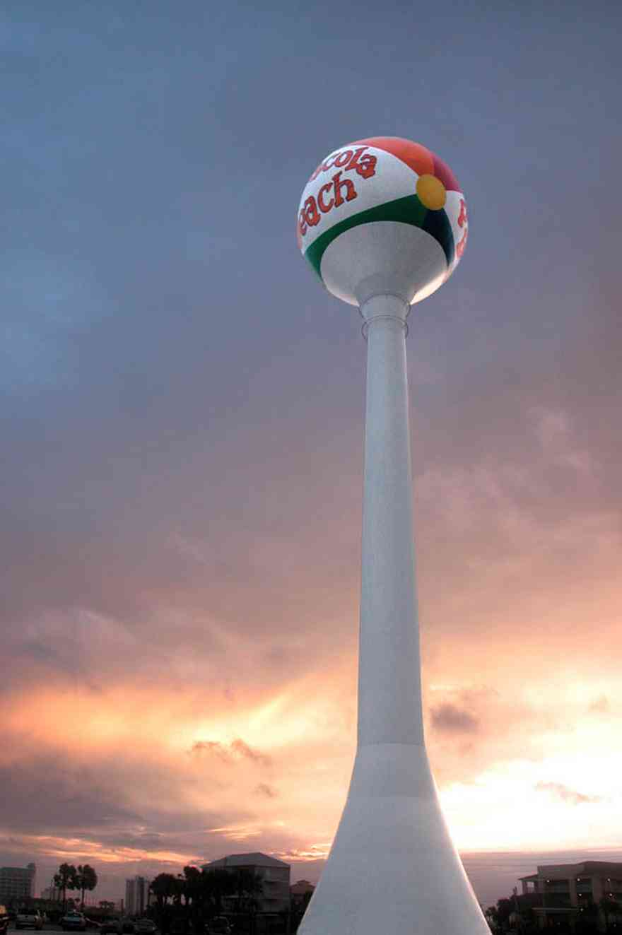 Pensacola-Beach:-Beach-Ball_01.jpg:  beach ball, water tower, tropical storm, mixed skies, palm trees, casino beach, parking lot,
