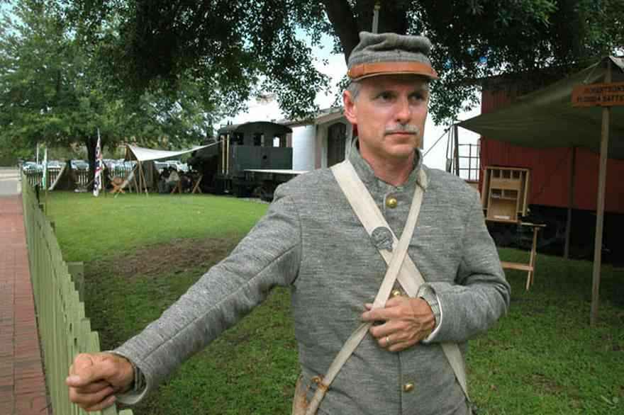 Pensacola:-Historic-Pensacola-Village:-Museum-Of-Industry_01a.jpg:  civil war soldier, museum, colonial village, historic reenactment, picket fence, brick sidewalk