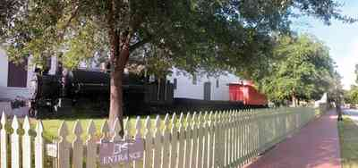 Pensacola:-Historic-Pensacola-Village:-Museum-Of-Industry_02.jpg:  locomotive, caboose, oak tree, picket fence, brick sidewalk