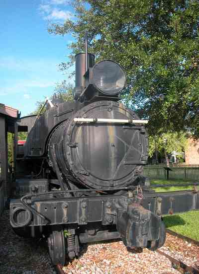 Pensacola:-Historic-Pensacola-Village:-Museum-Of-Industry_04.jpg:  locomotive, caboose, oak tree, picket fence, brick sidewalk
