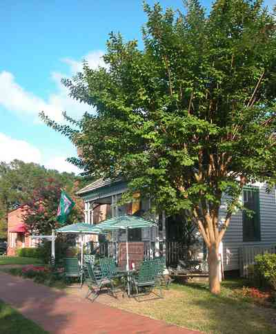 Pensacola:-Historic-Pensacola-Village:-The-Moreno-Cottage_03.jpg:  cafe, victorian cottage, shotgun cottage, crepe myrtle tree, umbrella table, brick sidewalk, cedar shake roof