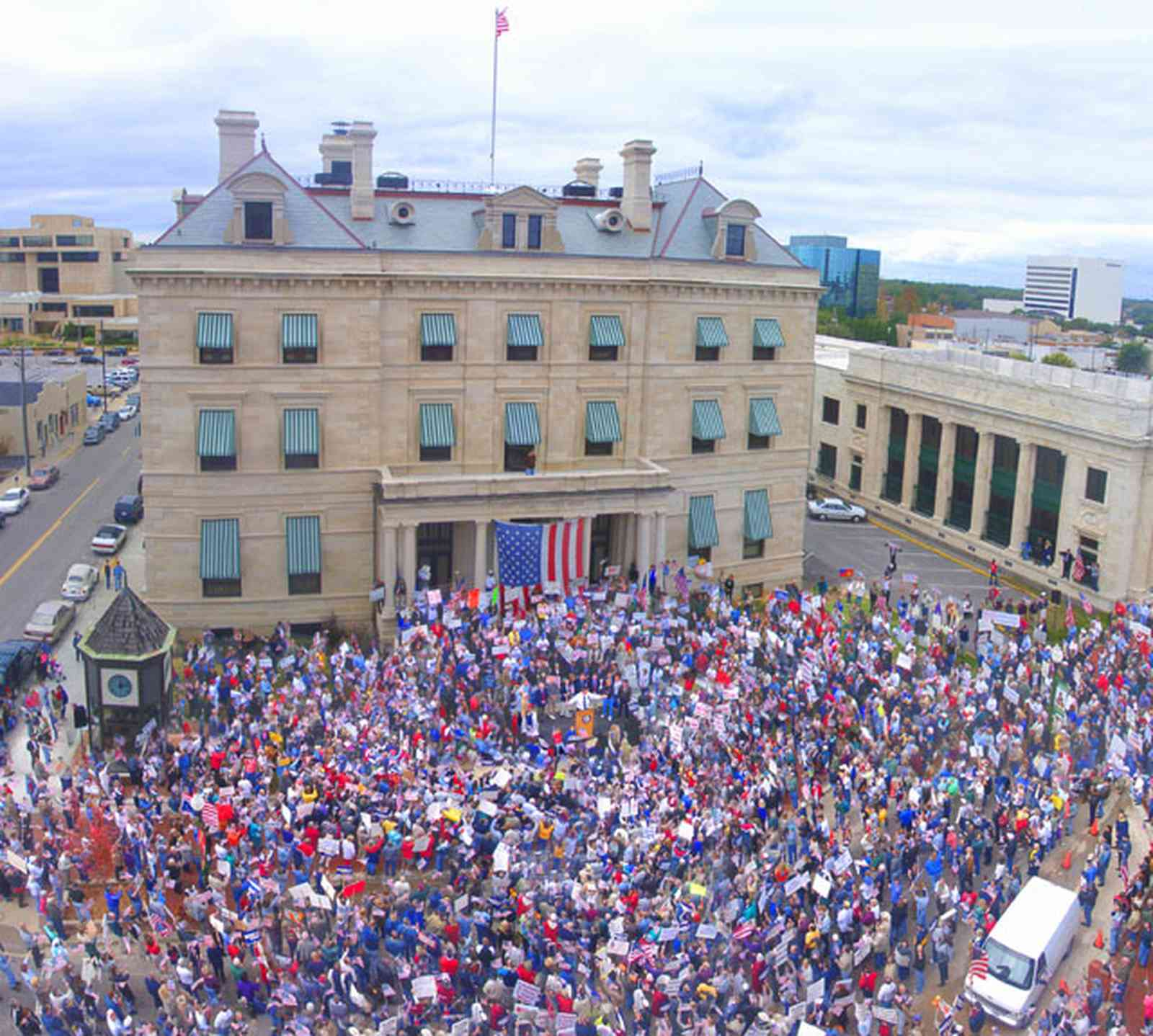 Pensacola:-Palafox-Historic-District:-Escambia-County-Courthouse_01.jpg:  escambia county courthouse, rally, awnings, renaissance revival architecture, american flag, crowd