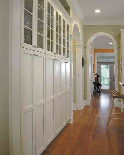 Pensacola:-Seville-Historic-District:-202-Cevallos-Street_14.jpg:  heart pine flooring, kitchen cabinets, hall, arcade, arched doorway, columns, storage space