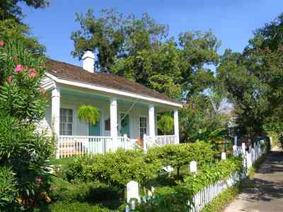 Pensacola:-Seville-Historic-District:-211-South-Florida-Blanca-Street_05.jpg:  creole cottage, picket fence, wood shingle roof, fern, oleander bush
