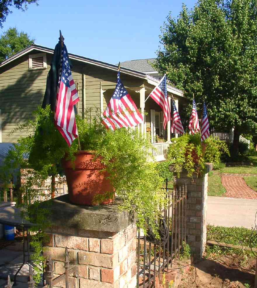 Pensacola:-Seville-Historic-District:-215-Cevallos-Street_.jpg:  american flag, wrought iron fence, creole cottage