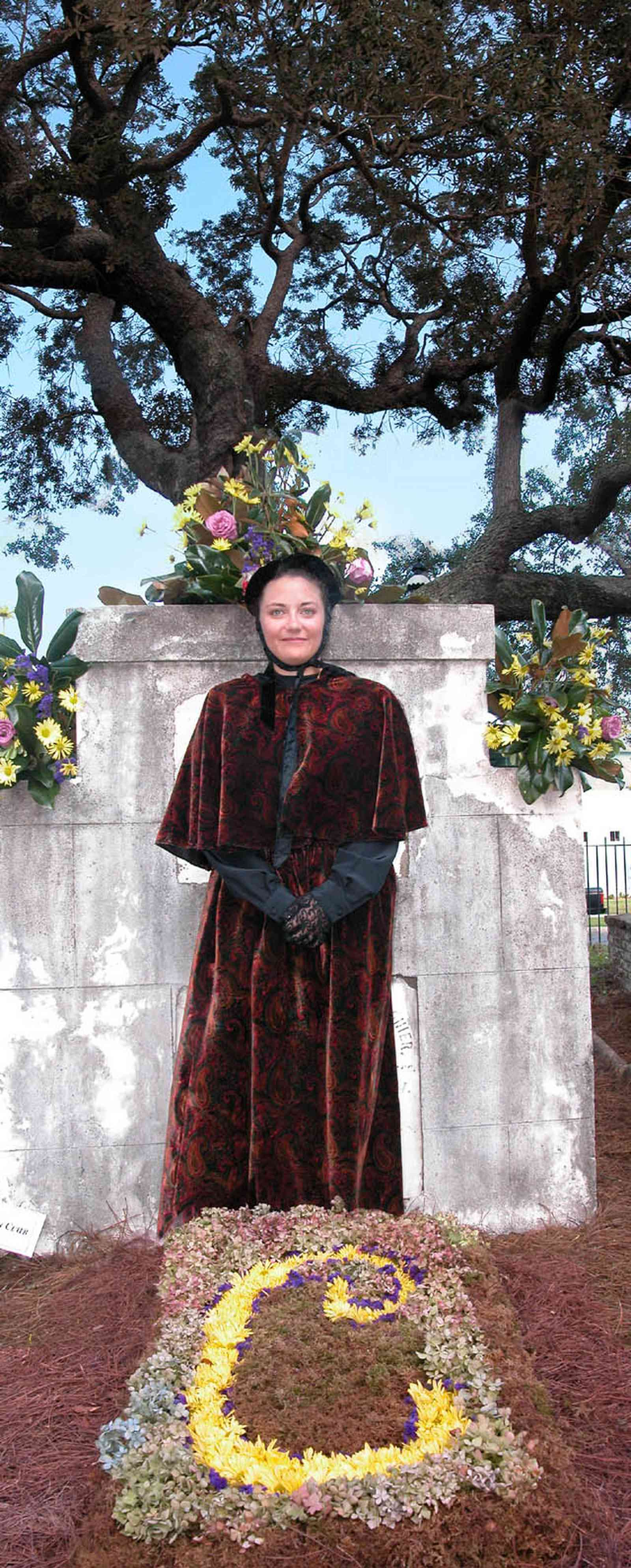 Pensacola:-Seville-Historic-District:-St-Michael-Cemetery_32.jpg:  floral tribute, velvet dress, gravesite, bonnet, oak tree, grave marker, monument