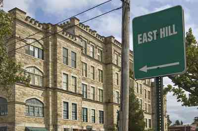 East+Hill_01+WEB.jpg:  sign, historic neighborhood, hospital, romanesque architecture, rough-cut stones, rounded arches, crenelated parapets,