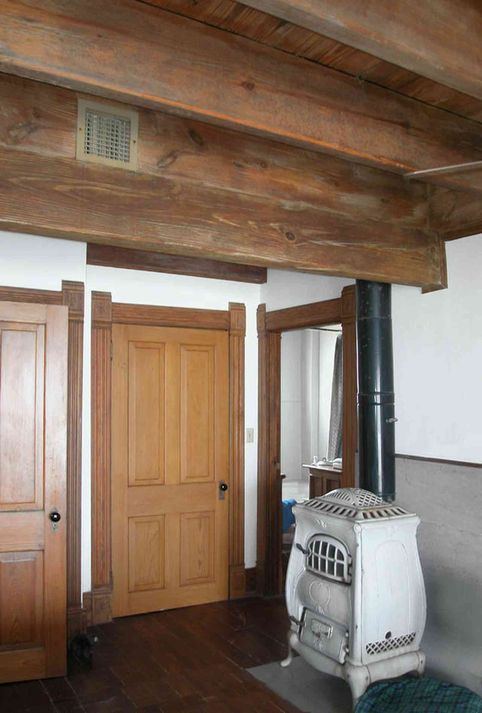 Perdido-Key:-Gothic-House_08p.jpg:  potbelly stove, heartpine lumber, bedroom, ceiling beams, marble facing