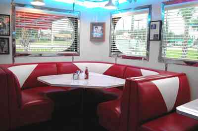 Pine-Forest:-50s-Diner_09.jpg:  booth, stainless steel trim, rainbow juke box, diner, hamburgers, malts