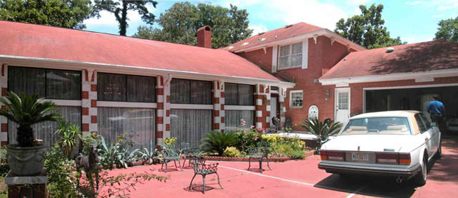Scenic-Highway:-3780-Scenic-Ridge-Drive_02a.jpg:  red brick house, colonial style architecture, rolls royce, patio furniture, sego palm tree, red concrete