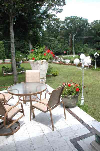 Scenic-Highway:-3780-Scenic-Ridge-Drive_31.jpg:  veranda, front porch, pot of geraniums, glass top table, lawn furniture,