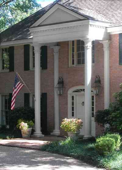Scenic-Highway:-4240-Bohemia-Drive_03.jpg:  columns, shutters, pediment, brick house, american flag, lanterns, oak trees, subdivision