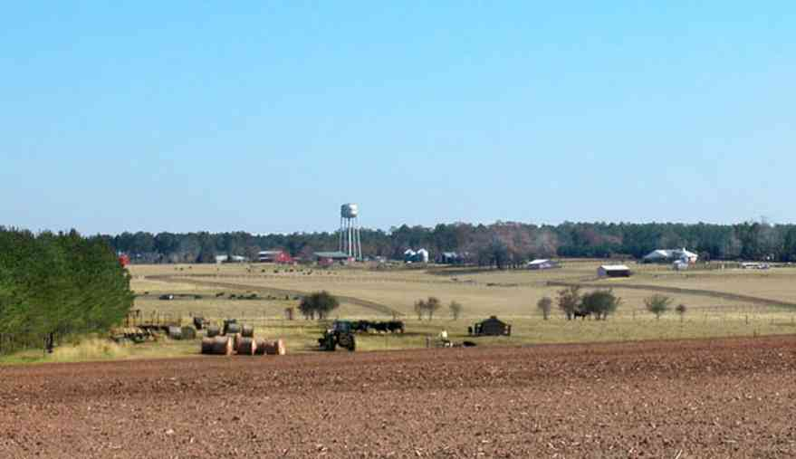 Walnut-Hill:-Cunningham-Farm_00a.jpg:  farm, fields, cattle, water tower, barns, fence, bales of hay, pine trees, plowed fields, rolling land, valley, ,